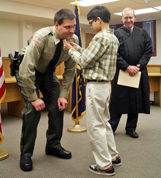 Matt English receives his sheriff designation pins from son Ben as Judge Donald Hull watches.