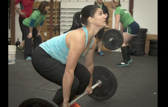 Katie Christopherson concentrates on a lift as she competes in the final workout during a Crossfit competition in The Dalles Saturday, Jan. 12. The regional competition was part of a world wide Crossfit competition, and featured three workouts, using Kettle bells, pull ups, wall balls and more. Mark B. Gibson photo