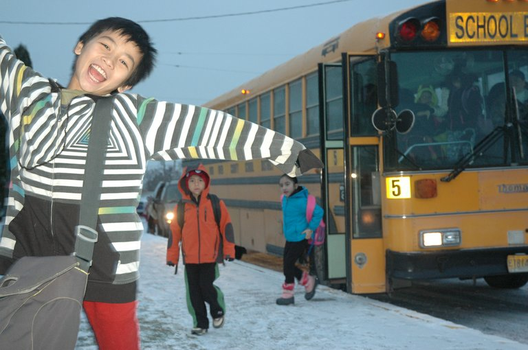 WITH A fresh coating of snow on the ground Thursday, school buses arrive at May Street School, where fifth-grader Rayne Melby is clearly happy to be.