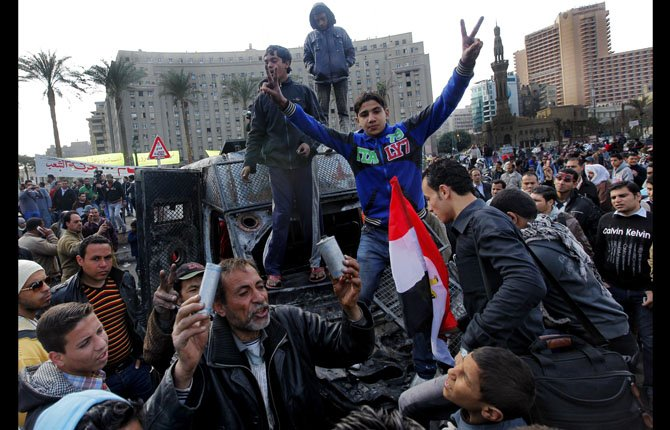 "Egyptian protesters celebrate the capture of a state security armored vehicle that demonstrators commandeered during clashes with security forces and brought to Tahrir Square in Cairo, Egypt, Tuesday, Jan. 29, 2013. Egypt's army chief warned Tuesday of the ""the collapse of the state"" if the political crisis roiling the nation for nearly a week continues, but said the armed forces will respect the right of Egyptians to protest. (AP Photo/Amr Nabil)"