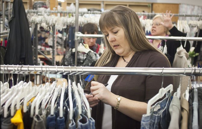 Vanessa Smith prices clothing at Saint Vincent dePaul in The Dalles. Most of the items being prepared to go out on the floor were donated in the summer. Mark B. Gibson photo