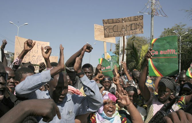 MALIANS DEMONSTRATE Dec. 8 in favor of an international military intervention to regain control of the country's Islamist-controlled north, in Bamako, Mali. They carry signs that say 'That's enough, let the government work' right, and 'We Malians Demand Chapter 7,' center, referring to the chapter of the United Nations Charter which would be used to authorize international military intervention. The spread of al-Qaida-linked militants across Libya, Algeria and Mali reflects a rise in local extremists who have been emboldened since the attack last Sept. 11 on a U.S. diplomatic post in Benghazi.	AP Photo/Harouna Traore
