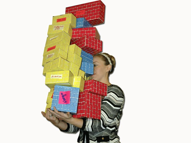The load can be lightened with guidance in life skills. Justine Ziegler of BBBS holds blocks representing life's challenges.