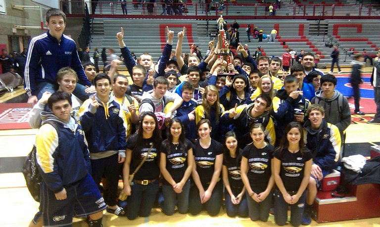 Proud of a first-place finish, the HRVHSwrestlers celebrate with their new trophy.