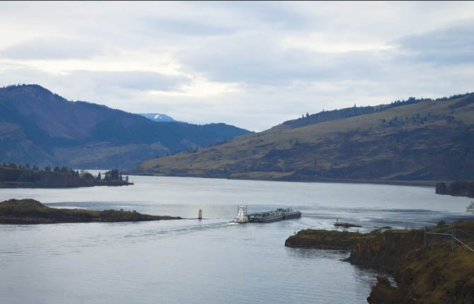 A BARGE moving down the Columbia River Feb. 6 passes between an island offshore of Oregon's Memaloose Park and the Washington shore. Photographed from Chamberlain Lake Rest Area on Highway 14, looking west.