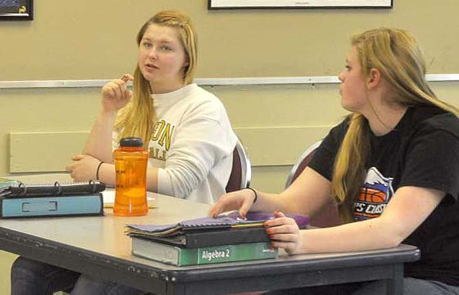 JUNIOR KALI Busler, left, asks a question of teacher Gerald Casper during afternoon math class at Sherman Junior-Senior High School Jan. 7 as sophomore Katie Asher listens.