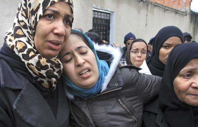 TUNISIAN WOMEN gather Feb. 8 in front of the house of slain opposition leader Chokri Belaid's father prior to his funeral in Tunis. Tunisia braced for clashes on Friday, with the capital shut down by a general strike and the army deployed for the funeral of a slain opposition leader expected to draw tens of thousands of mourners, and potentially many more.