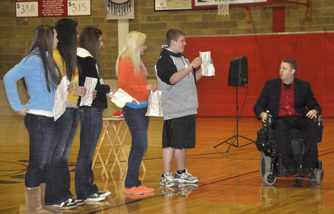 Jake French, right, has Dufur high school students help him demonstrate that people are never quite the same after being bullied, just like a piece of paper is never quite the same after being crumpled up. French, an inspirational speaker who once attended Dufur, returned to the school Monday to teach students about achieving happiness no matter what happens to them.