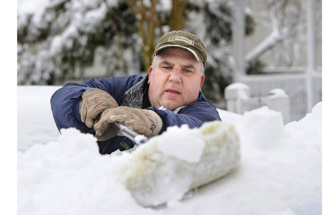Hank Luth brushes snow piled high on his car parked in his driveway on Terry Ct. after a snow storm Feb. 9 in Glen Head, N.Y.