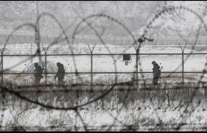 South Korean army soldiers patrol along barbed-wire fences at the Imjingak Pavilion, near the demilitarized zone of Panmunjom, in Paju, South Korea, Tuesday, Feb. 12, 2013. South Korea is confirming that North Korea has tested a nuclear device in defiance of U.N. orders to stop building atomic weapons. 	