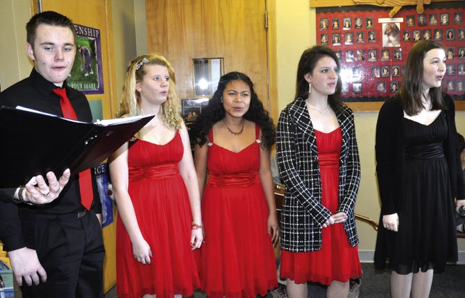 "The Harmonaires, a jazz choir from The Dalles Wahtonka High School, have been spreading cheer around town with musical Valentines, including this rendition of ""Pretty Little Angel Eyes"" in the Chenowith Elementary School front office on Feb. 13. From left to right are Quinn Farquharson, Hannah Lupkes, Madeleine Morgan, Kellina Coy and Kathleen Albrecht.	Photo by Jade McDowell"