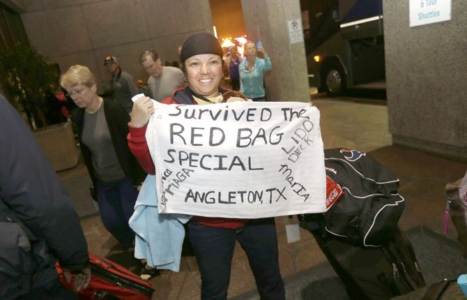 Veronica Arriaga, of Angleton, Texas, a passenger from the disabled Carnival Triumph cruise ship, holds a sign referring to the red biohazard bags used as toilets, after arriving by bus at the Hilton Riverside Hotel in New Orleans, Friday, Feb. 15, 2013. The ship had been idled for nearly a week in the Gulf of Mexico following an engine room fire.