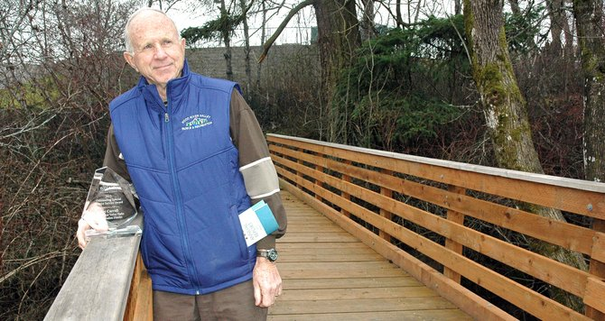 Parks volunteer Art Carroll with his SDAO award, on the bridge over Indian Creek at Columbia Gorge Community College, one of the trail route features he helped organize and construct.