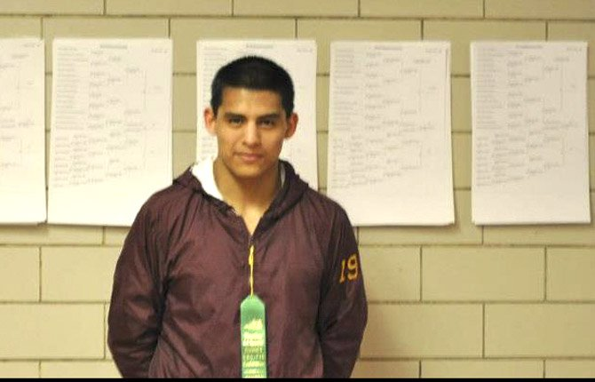 TDW grappler Eric Morales proudly displays his fourth-place ribbon, which put him into the state pool. The junior had four wins to earn his trip.