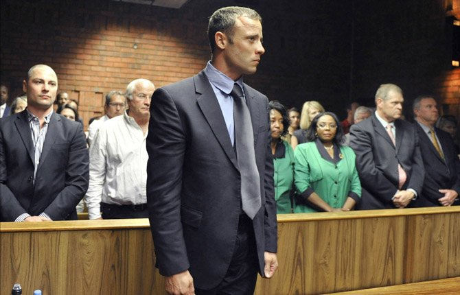 Olympian Oscar Pistorius stands following his bail hearing in Pretoria, South Africa, Tuesday, Feb. 19, 2013. Pistorius fired into the door of a small bathroom where his girlfriend was cowering after a shouting match on Valentine's Day, hitting her three times, a South African prosecutor said Tuesday as he charged the sports icon with premeditated murder. The magistrate ruled that Pistorius faces the harshest bail requirements available in South African law. He did not elaborate before a break was called in the session.
