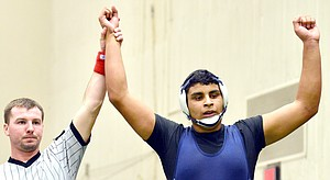 Juan Karlos Hernandez has his arms raised in victory after winning a preliminary round match at the 2013 Special district II wrestling championships. Hernandez took second place in the 200 pound weight class.