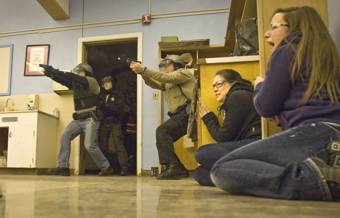 "STUDENT ACTORS Shaela Buchanan, right, and Aubrey Hanson cower near a doorway as area officers attack a gunman during a ""live shooter"" training session Wednesday at the old Chenowith Middle School building in The Dalles."
