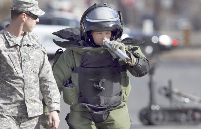A MEMBER of a bomb disposal squad smells the contents of a suspicious pipe found on East H Street in Yakima, Wash., Feb. 21. The pipe, found lying next to a house, was moved and then detonated by the Army unit based at the Yakima Training Center. The pipe was found to be stuffed with marijuana.