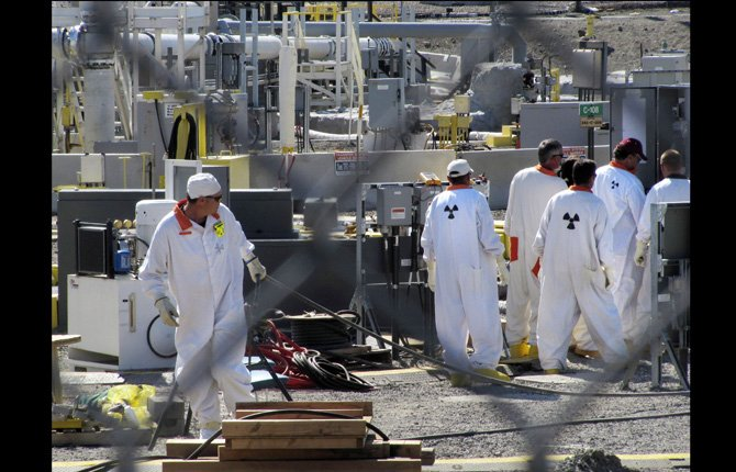Workers at the Hanford nuclear reservation work around a a tank farm where highly radioactive waste is stored underground near Richland, Wash. Six underground radioactive waste tanks at the nation's most contaminated nuclear site are leaking, Gov. Jay Inslee said Feb. 22.