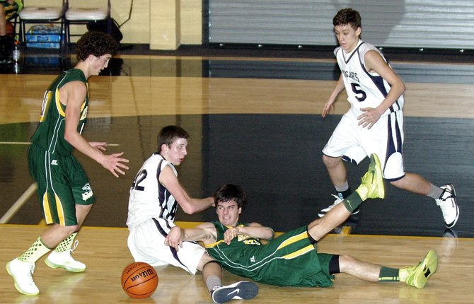 SOUTH WASCO'S David Ocacio (middle) and teammate Loreto Morelli converge on a loose ball in front of Country Christian's Luke Carter (on ground) and Jordan Syphard in second-half state playoff action Friday night in Mollala. The Cougars used a buzzer-beating 3-pointer by Cooper Nofziger to win, 50-47.