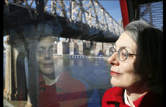 Janet Falk, public relations professional, rides the Roosevelt Island tramway with a Manhattan view behind her Feb. 21.  Falk applied for a public-relations job at a New York City law firm two years ago, but the recruiter told her she wouldn't be considered because she had been unemployed for more than three months, Falk said.