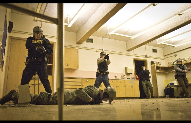 "A DEPUTY, at left, covers a fallen ""shooter"" as additional officers move to search the room before responding to a second ""shooter"" in a nearby classroom. The training was held at the old Chenowith Middle School."