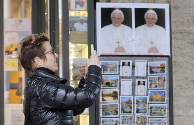 A woman takes photos next to portraits of Pope Benedict XVI, outside a bookshop near the Vatican Feb. 26. Pope Benedict XVI will be known as emeritus pope in his retirement and will continue to wear a white cassock. 	