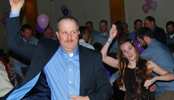 Eric Bokovy shows his daughters Jude, 11 (pictured) and Claire some wild steps at the YoungLife Father Daughter Dance Feb. 23, 2013.