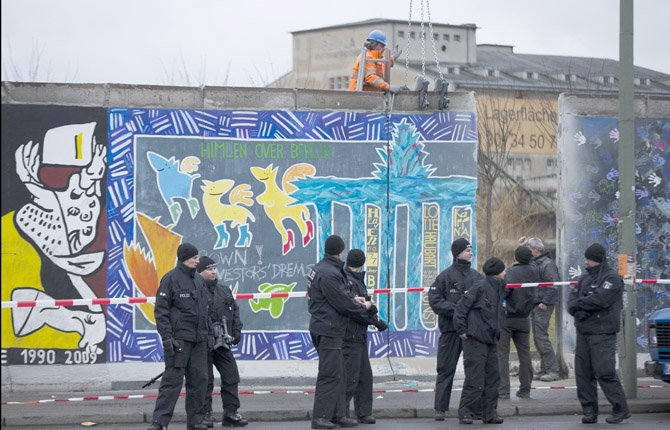 German police officers protect a part of the former Berlin Wall and a construction worker who fixed a part of the wall at a crane in Berlin, Germany, March 1. Construction crews stopped work Friday on removing a small section from one of the few remaining stretches of the Berlin Wall to make way for a condo project after hundreds of protesters blocked their path. 	