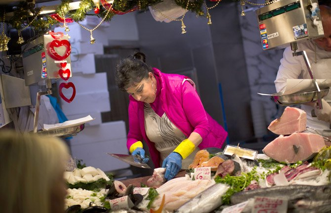 A fishmonger prepares fish for a client in a market in Barcelona, Spain. Mediterranean diets have long been touted as heart-healthy, but that's based on observational studies. Now, one of the longest and most scientific tests suggests this style of eating can cut the chance of suffering heart-related problems, especially strokes, in older people at high risk of them.