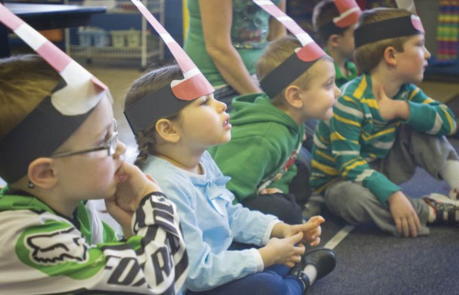 PRESCHOOL STUDENTS at Saint Mary's Academy listen with great interest as a Read Across America volunteer shows them a picture book March 1 about one young boy's wacky day. Volunteers read in all of the elementary schools in the area throughout Friday.
