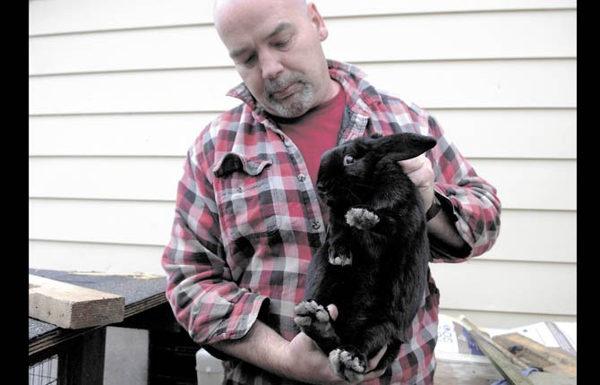 Tony Chatman holds a black rabbit in his yard in Oregon. He is a member of Southwestern Oregon Preppers, a group of about 100 people that prepares for events such as natural disasters or chemical attacks. Chatman keeps rabbits and chickens in his backyard for food in case of a disaster. He says rabbit can be used for rabbit noodle soup.