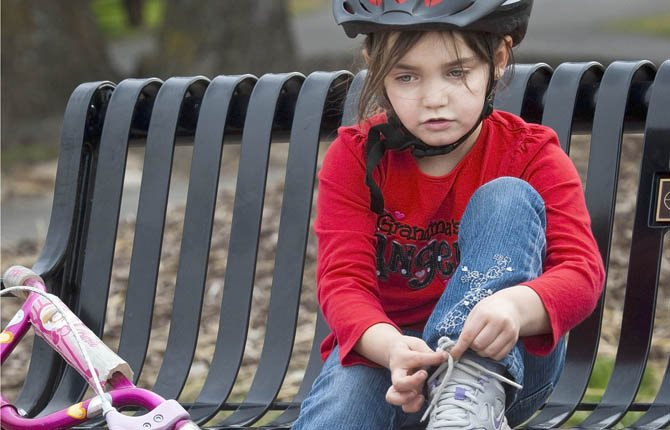 KAYLEE WOODMAN, 6, ties her shoe before embarking on a bike ride on the Riverfront Trail at Klindt's Cove pocket park Saturday, March 3.