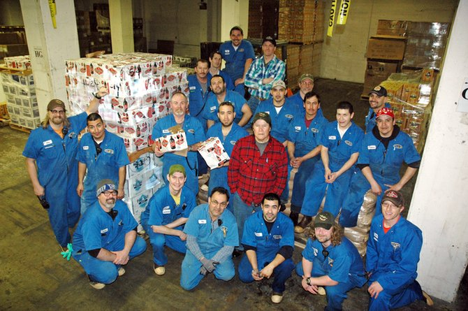 Most of the Full Sail flood crew gathered Thursday next to a pallet of damaged beer. Front row, kneeling: Barney Brennan, Chris Haveman, Eloy Pondo, Juan Manuel Rodriquez, Clinton Wertzbaugher, Dave Ashburn; second row: Chris Davis, left, Francisco Martinez, Wendell Bryant and Francisco Robles holding beer, Maximo Villafana in checked coat; third row Angel Sanchez, Jose Castillo, Vicente Castro, Elias Barron, Gabriel Uvale; in back: Leo Torres, Collin Godkin, Gavin Lord. Mark Yeoman, Phil Roche, Jason Munoz.