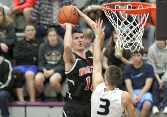 Matt Totaro shoots an inside jumper over Hosanna defender Tayler Coler during the Hawks' 58-37 semifinal state tournament win Friday in Baker City. Totaro finished the game with 21 points and was named to the all-tournament team.