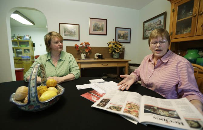 Kimberly Bliss, left, and her wife Kim Ridgway, right, look at recepies for marijuana &quot;edibles&quot; as they sit at their dining room table Feb. 27, at their home in Lacey, Wash. The couple got married on Dec. 9, 2012, thanks to the states new gay marriage law, and now they are trying to take advantage of another measure voters approved in November by planning to open a state-licensed marijuana store. 	