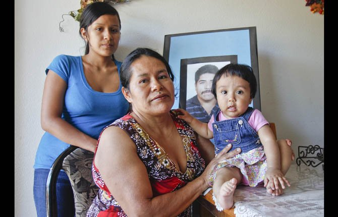 Juana Garcia Martinez, with her daughter, Gladys Dominguez, 19, left, and granddaughter, Jazleen Dominguez, 8-months-old, pose in front of a photo of Juana Garcias late husband, Ildefonso Martinez, in Vista, Calif. Ildefonso Martinez died from dehydration trying to cross back into the United States after being deported.	