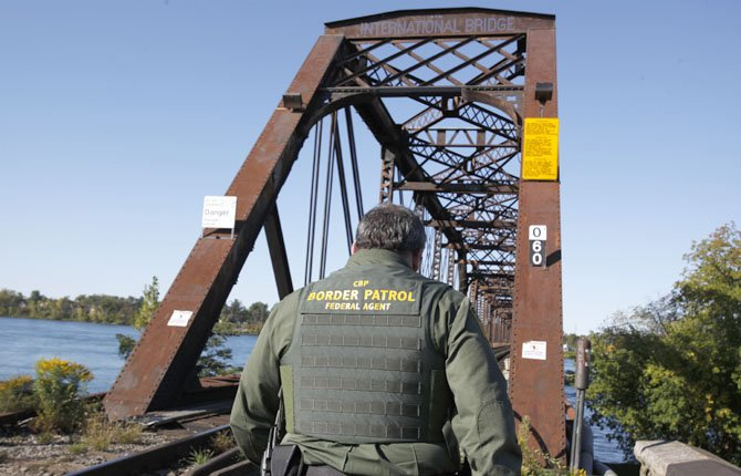 Senior Border Patrol Agent Sheldon Cooper monitors the International Railroad Bridge in Buffalo, N.Y. Government agencies vary widely in how they are dealing with $85 billion in across-the-board budget cuts.