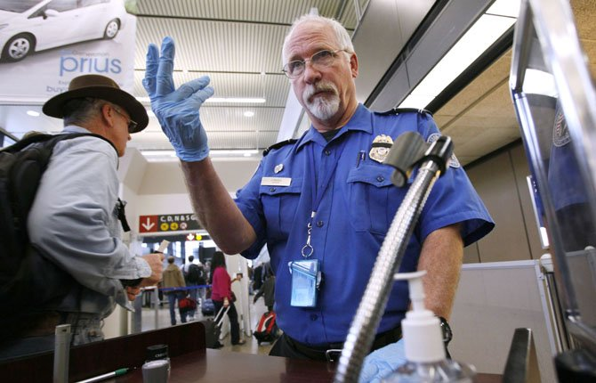 TSA OFFICER Robert Howard signals an airline passenger forward at a security check-point Jan. 4 at Seattle-Tacoma International Airport in SeaTac, Wash. Flight attendants, pilots, federal air marshals and even insurance companies are part of a growing backlash to the Transportation Security Administration's new policy allowing passengers to carry small knives and sports equipment like souvenir baseball bats and golf clubs onto planes.