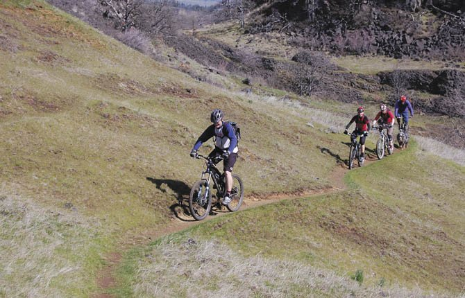 Mountain bikers ride a trail at the Mosier Syncline.