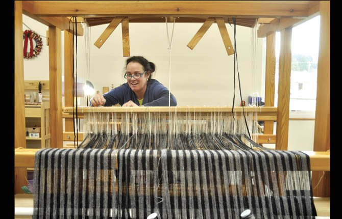 KATHY SEMMES uses a loom of Skandinavian design to weave a black and gray design of alpaca yarn. It is quieter and requires a lighter touch on the foot pedals than some other looms.