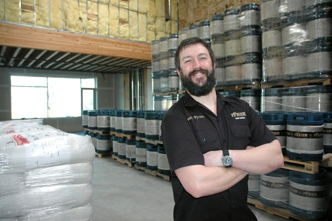 Josh Pfriem stands next to barrels in the new section of his brewery.