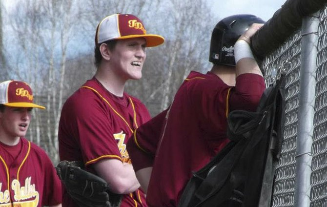 THE DALLES WAHTONKA pitcher Dakota Walker (middle) surveys play from the dugout with teammate Kaci Kiser (left) in Monday's 5A baseball game versus Marist in Eugene. Walker, who is in remission from Burkitt's Leukemia, got the starting nod for his first live action on the diamond since April 2012.