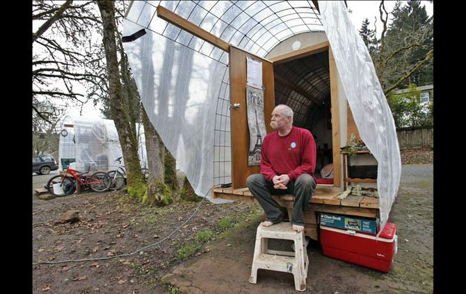 Mark Hubbell sits on the porch of his Conestoga Hut, in the parking lot of the Episcopal Church of the Resurrection in Eugene. The shelter is one of the first, small portable living structures for homeless people that has been built as part of a demonstration project by the City of Eugene and area shelter advocates.