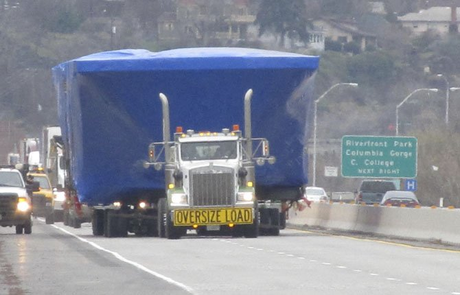 A WIDE, BLUE load delayed traffic on Interstate 84 through The Dalles Tuesday morning as a very slow delivery was under way to rural Roosevelt Lake. It was the main hull of the replacement Keller Ferry.