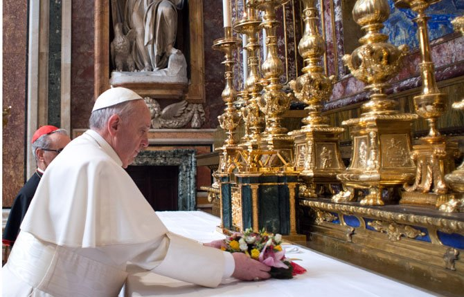 Pope Francis puts flowers on the altar inside St. Mary Major Basilica, in Rome, Thursday, March 14. Pope Francis opened his first morning as pontiff by praying Thursday at Rome's main basilica dedicated to the Virgin Mary, a day after cardinals elected him the first pope from the Americas.