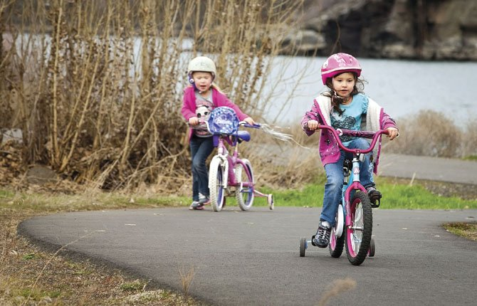 Brooklyn Strickland, right, and Tayten Sutherland, both 6, circle a small loop of the Riverfront Trail at Klindt's Cove in The Dalles. The trail access park is a popular area for those in town wanting to take advantage of the sometimes brief breaks in the cloudy spring weather.