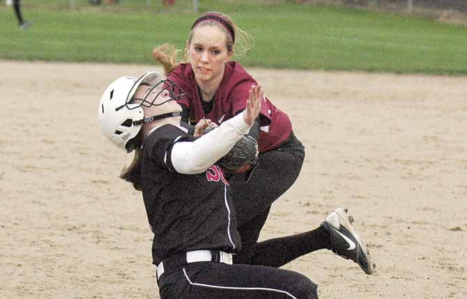TDW third baseman Morgan Goslin (top) makes a tag on Sandy runner Rachell Rutledge during the third inning of Fridays softball game at 16th Street Ballpark. The Pioneers scored four runs in the third frame and won, 5-2.   	                            