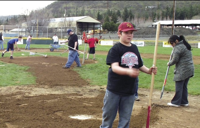 Justin Eiesland flips a pebble off the diamond near home plate as he and a host of other volunteers work to get Kramer Fields in shape for the coming Little League season. Opening day is April 13, but some teams will see action before that date.