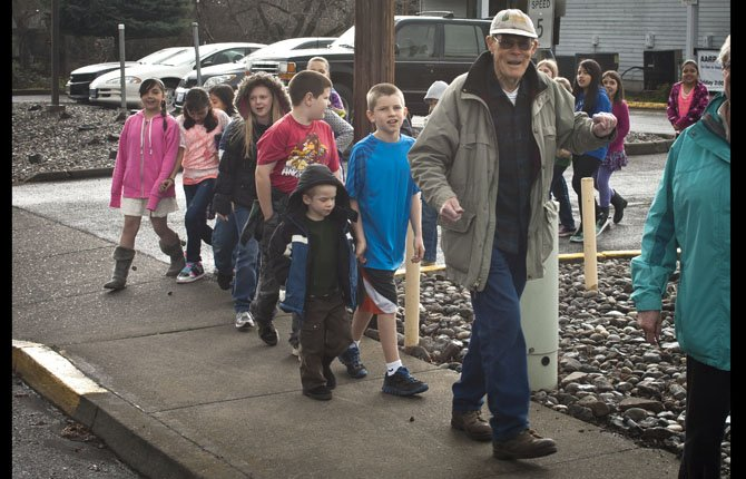 YOUNG STUDENTS follow Jim Holston as he participates in a march against senior hunger Thursday, March 21,  around the Mid-Columbia Senior Center in The Dalles.